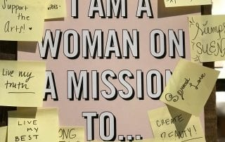 "A sign with the text ""I am a woman on a mission to..."" with post-it notes with multiple examples of goals to accomplish"